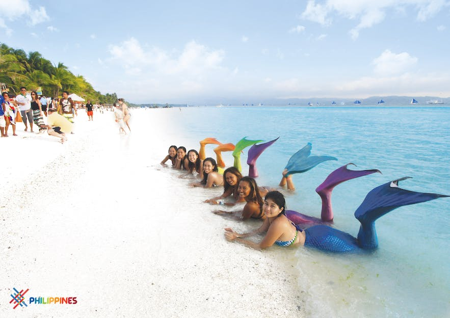 Several tourists taking a photo while wearing their mermaid costume in Boracay