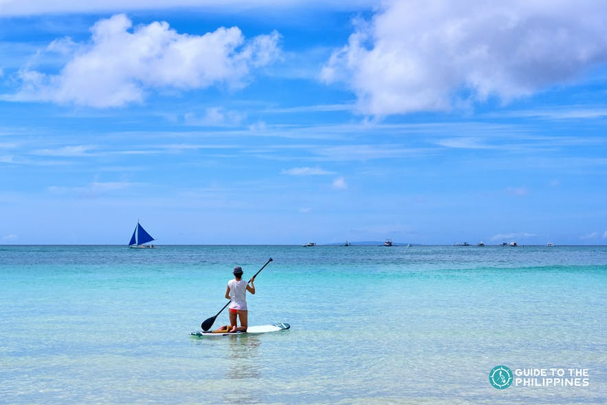A woman paddleboarding in the blue waters of Boracay