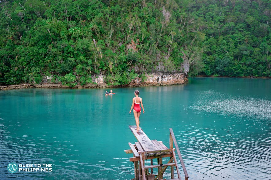A girl about to jump from a diving board in Sugba Lagoon
