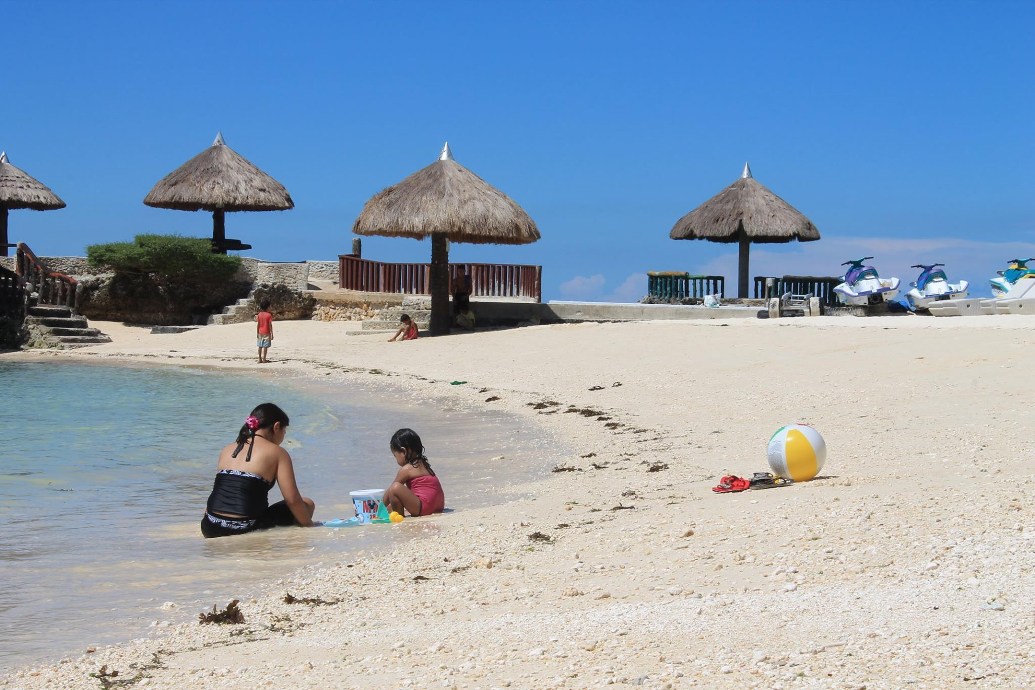 Kids playing with sand in front of a resort in Camotes Island