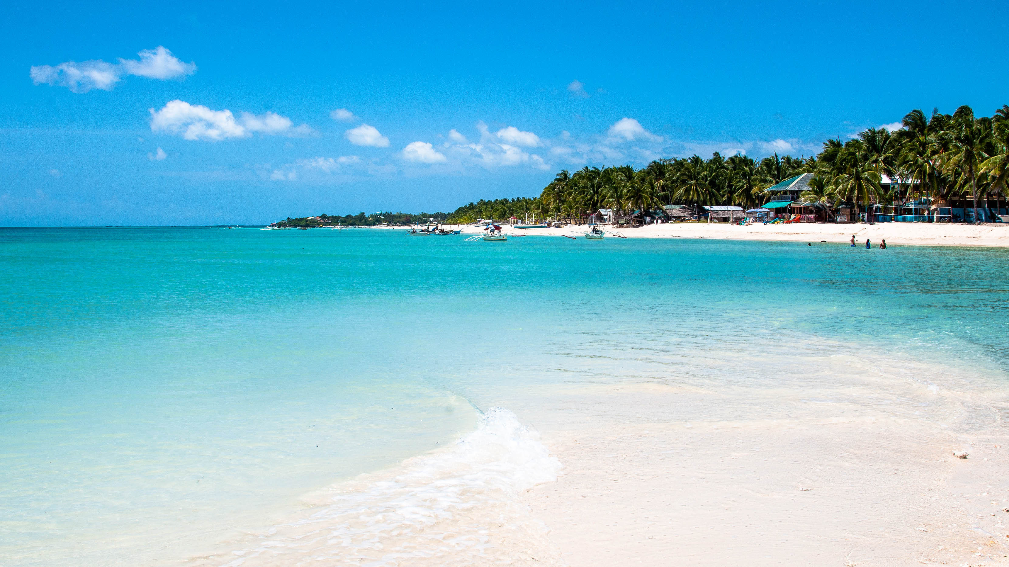 Clear blue waters and white sand at a beach in Bantayan Island
