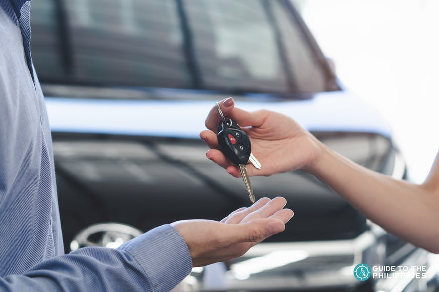 Car rental company handing over the keys to a customer