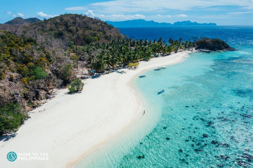 Aerial view of the white sand beach of Malcapuya Island