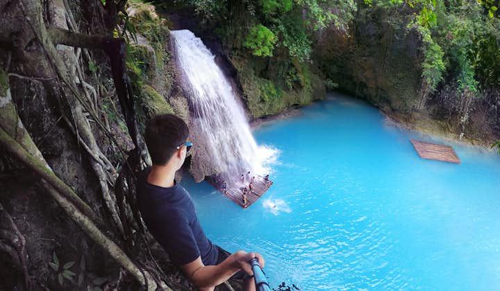 A man staring at the beauty of Kawasan Falls