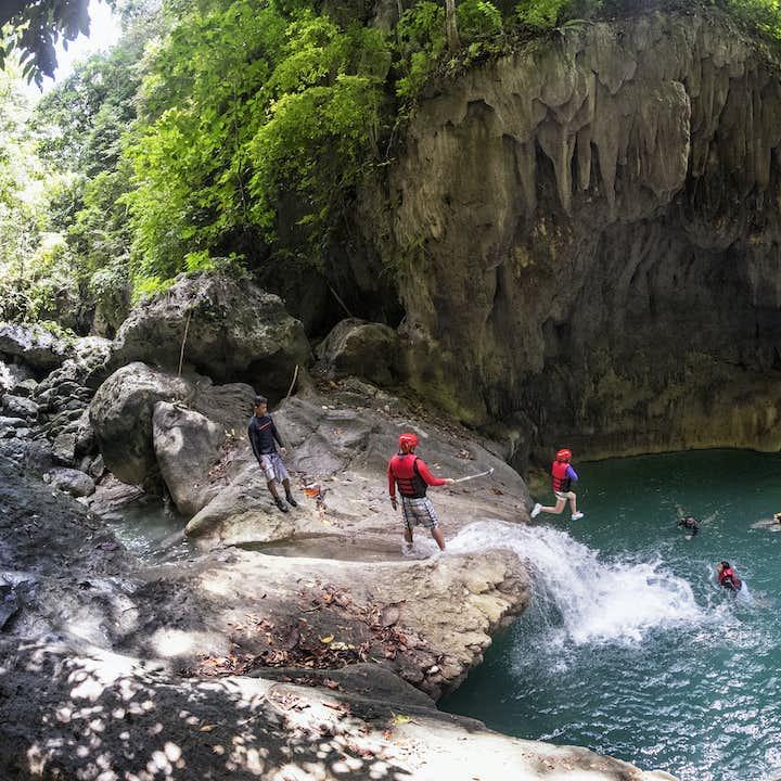 Tourists jumping during the Canyoneering experience at Kawasan Falls
