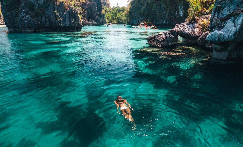 A girl floating on the waters of Big Lagoon in El Nido Palawan