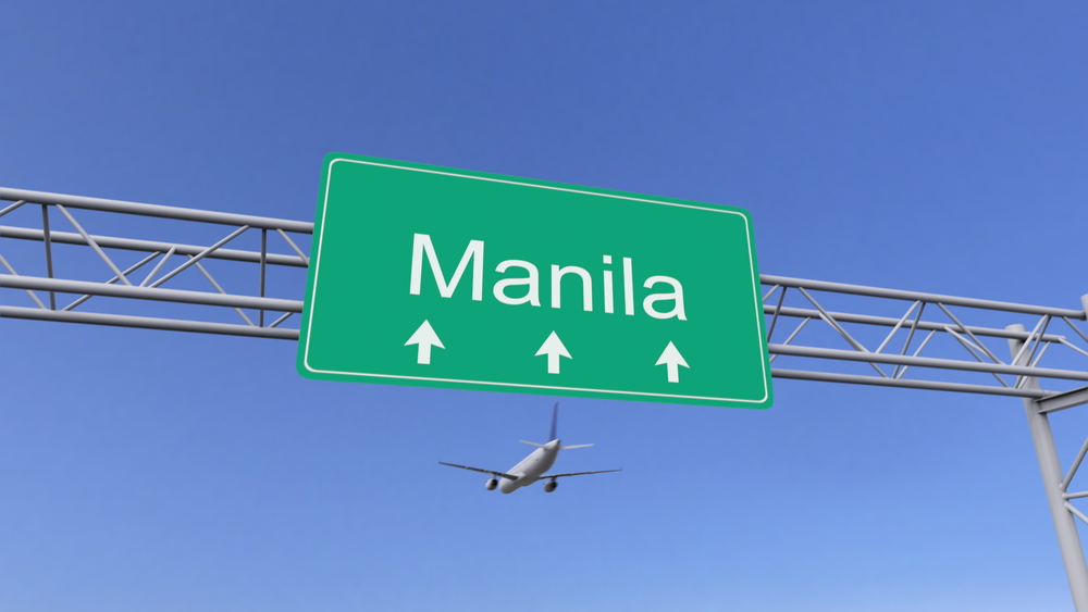 A plane flying over a Manila sign