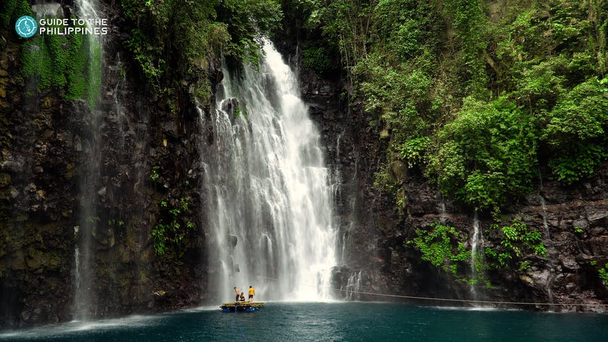 People standing on raft by Tinago Falls in Iligan City