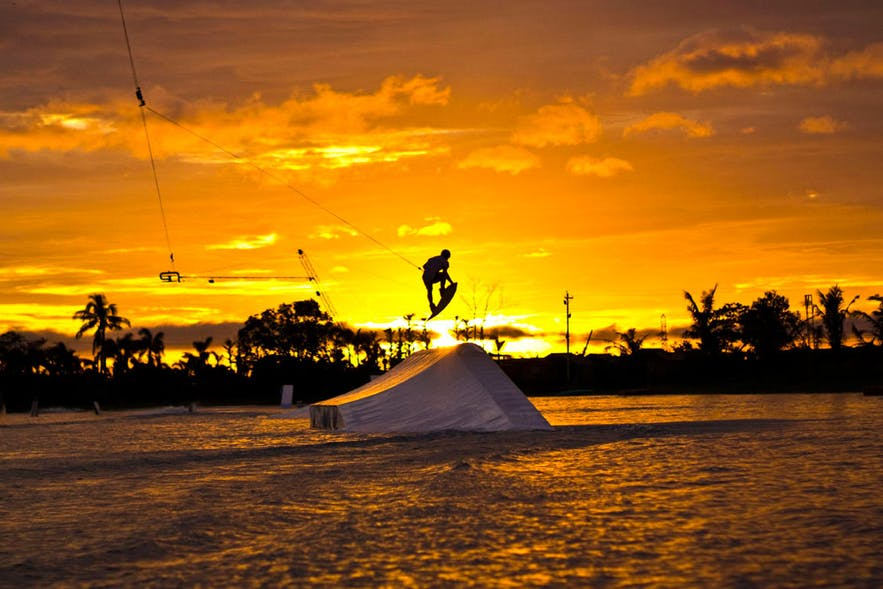 An athlete wakeboarding in CamSur Waterpark during sunset