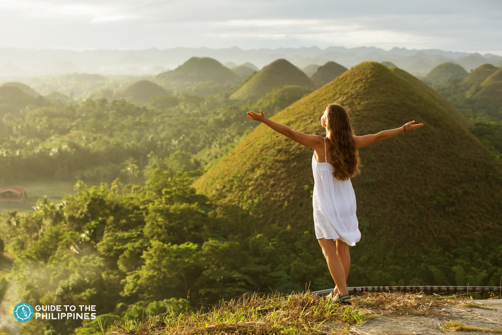 A woman enjoying the sunset at Chocolate hills in Bohol