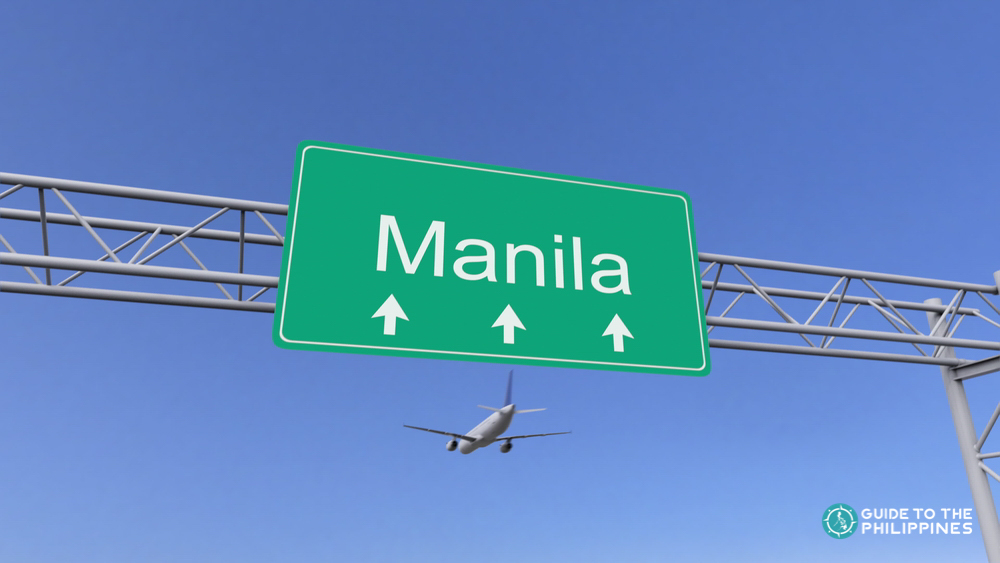 A plane flying over a signage of Manila near the airport