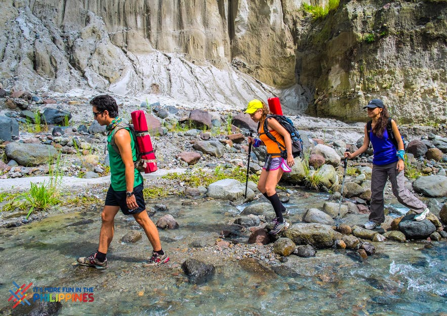Tourists trek across a stream in Mt. Pinatubo