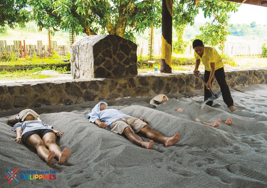 Tourists enjoying volcanic ash spa treatment