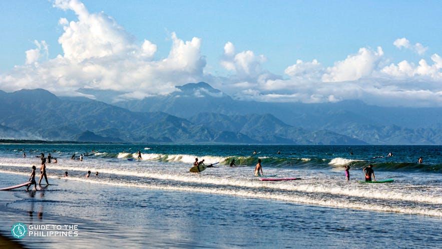 Tourists surfing in Sabang Beach, Baler