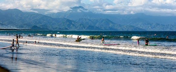 Tourists surfing in Sabang Beach, Baler.jpg