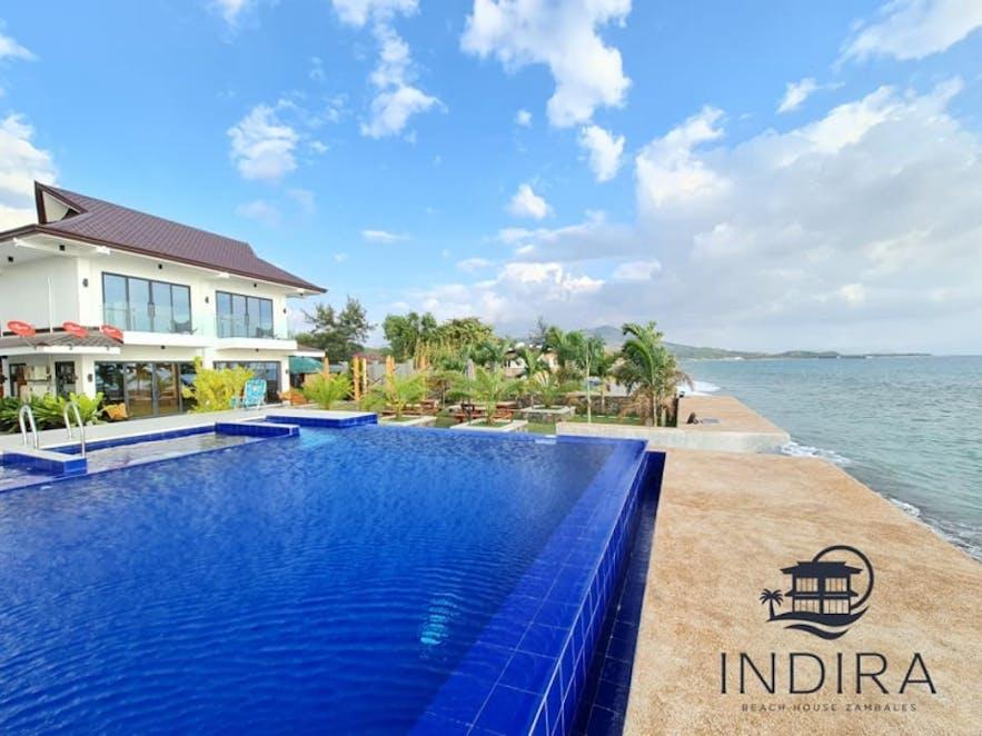 The pool and beachfront of Indira Beach House