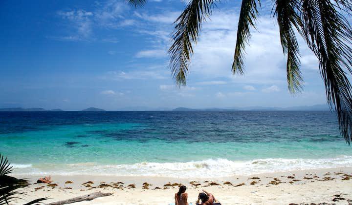 Two people enjoying a beach in Port Barton Palawan