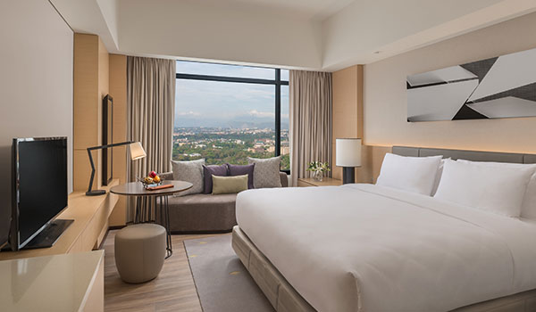 Enjoy the bed and the view of the city from your room in Seda Vertis North