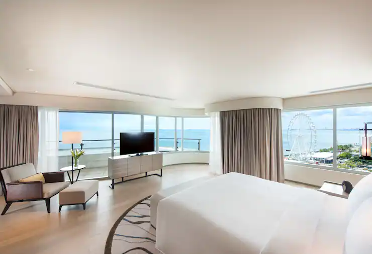 A bed facing the window with a beautiful view in Conrad Hotel