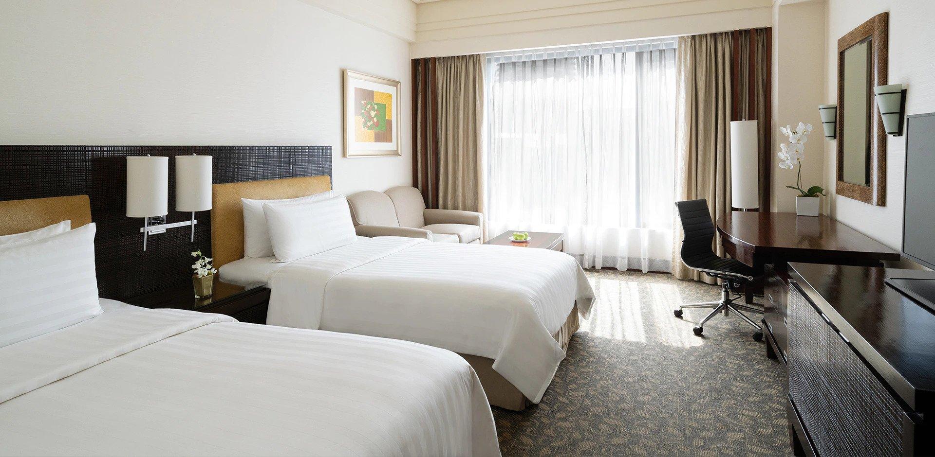 Twin beds inside a room in EDSA Shangri-la Hotel