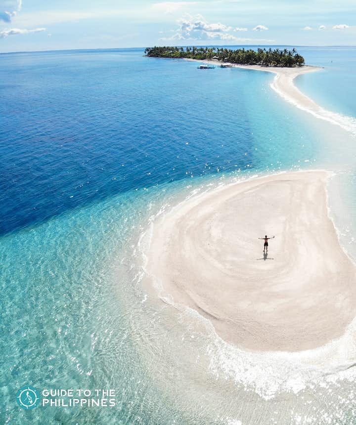 Tourist stands on Kalanggaman Island's sandbar