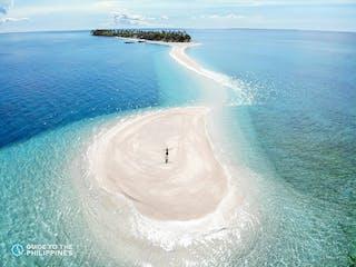 Tourist stands on Kalanggaman Island's sandbar.jpg
