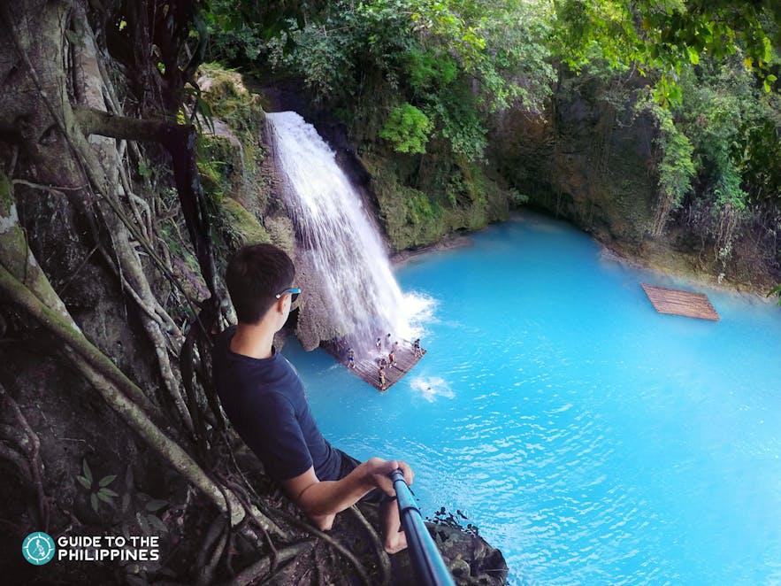 Man getting ready to cliff dive in Kawasan Falls