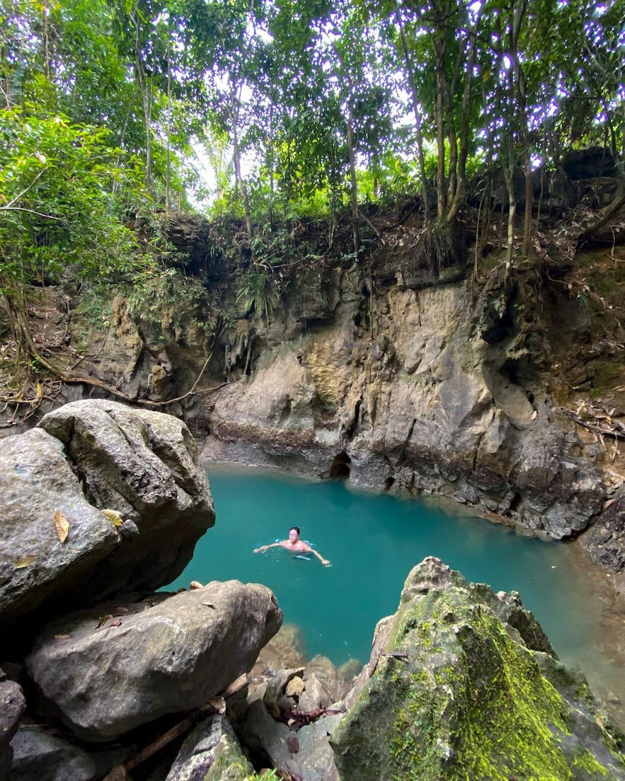 Tourist swims in the Tayangban Cave Pool